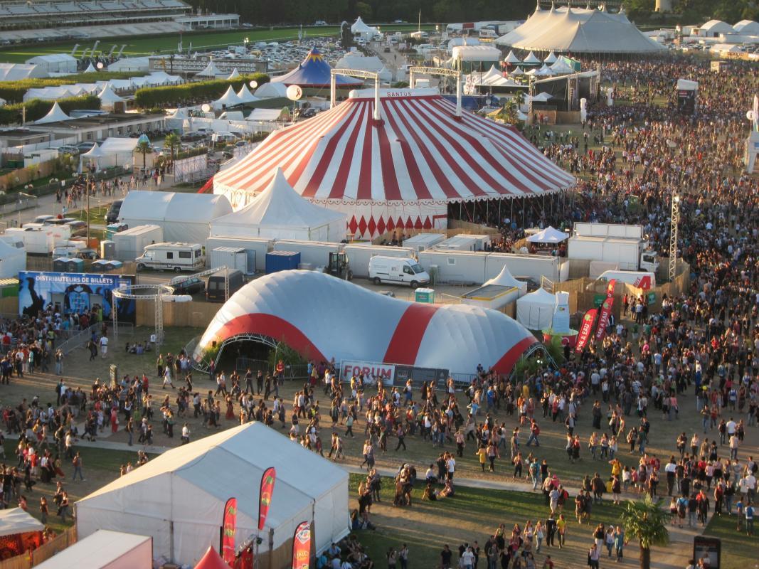 Vue aérienne du site du festival montrant la structure à la toile rouge et argent.