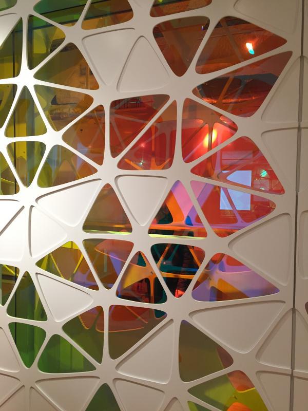 Habillage en panneaux perforés et remplissages en verre miroir dichroïque.