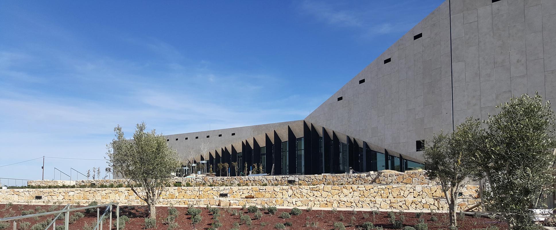 Façades vitrées et enveloppe en pierre du Musée Palestinien.