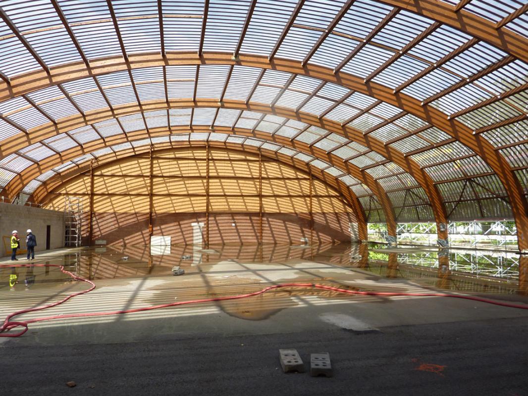 La charpente en bois lamellé collé de la halle de tennis en cours de construction.